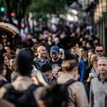 photo of a crowd of peoplke walking in the street